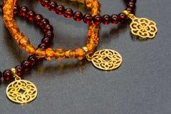 Bärnstensfärgade armband med guld- hängear royaltyfria foton