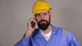 Bärtige Arbeitskraft im gelben Sturzhelm sprechend am Telefon mit jemand auf grauem Hintergrund stock video footage