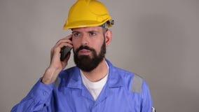 Bärtige Arbeitskraft im Sturzhelm sprechend am Telefon mit jemand auf grauem Hintergrund stock video footage