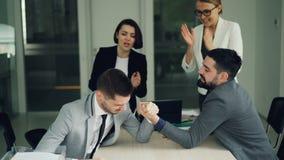 Bärtige Büroangestellte der jungen Leute haben übendes Armdrücken des Spaßes, während Frauen sind, stützend aufpassend und sie stock footage