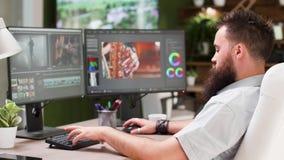 Bärtige Kerlarbeit als Videoherausgeber oder Farbenkünstler in der kreativen Medienagentur stock footage