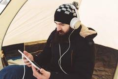 Bärtige Manngrifftablette und hören Musik auf Kopfhörern Lizenzfreies Stockbild