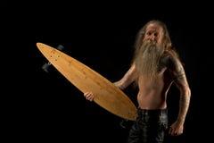 Bärtiger älterer Mann mit einem langen Brett Stockfoto