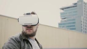 Bärtiger attraktiver Mann benutzt Gläser der virtuellen Realität auf dem Dach 4K Stockfotografie