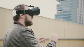 Bärtiger attraktiver Mann benutzt Gläser der virtuellen Realität auf dem Dach 4K Stockbilder