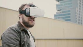 Bärtiger attraktiver Mann benutzt Gläser der virtuellen Realität auf dem Dach 4K Stockbild