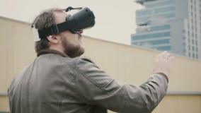 Bärtiger attraktiver Mann benutzt Gläser der virtuellen Realität auf dem Dach 4K Lizenzfreie Stockfotografie