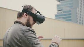 Bärtiger attraktiver Mann benutzt Gläser der virtuellen Realität auf dem Dach 4K Stockfotos
