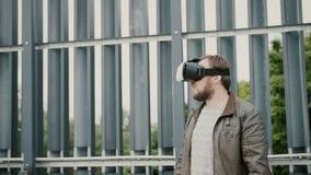Bärtiger attraktiver Mann benutzt Gläser der virtuellen Realität im Stadtgebiet 4K Lizenzfreie Stockfotos