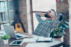 Bärtiger, attraktiver Mann, der im Büro vor Laptopsc sich entspannt Stockfoto