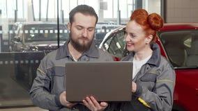 Bärtiger Automechaniker unter Verwendung des Laptops an der Garage, arbeitend mit weiblichem Kollegen stock video footage