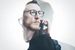 Bärtiger Banker der Doppelbelichtung, der schwarzes Hemd und die Gläser, zeitgenössische Smartphonehand halten trägt Lokalisierte stockfotos