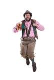 Bärtiger, bayerischer Kerl, der mit Weizenbier springt Lizenzfreies Stockbild
