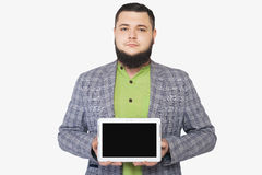 Bärtiger dicker Mann, der ein tragbares Gerät hält Stockbild