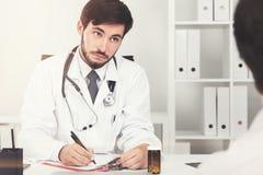 Bärtiger Doktor, der mit Patienten im Büro spricht Lizenzfreie Stockfotos