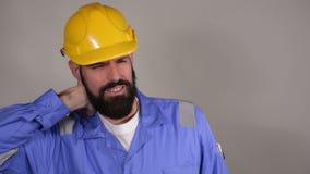 Bärtiger Erbauer oder Erbauer oder Vorarbeiter oder Schlosser in den gelben errichtenden Sturzhelmleidennackenschmerzen stock footage