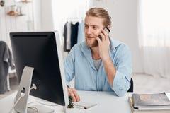Bärtiger erfahrener junger blonder Werbetexter arbeitet an neuem Artikel, Arten auf Tastatur, hat Telefongespräch, sich bespricht Lizenzfreies Stockfoto