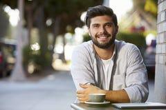 Bärtiger erwachsener Mann mit dem Laptop, der bei Tisch außerhalb des Cafés sitzt lizenzfreie stockbilder