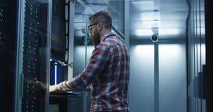 Bärtiger IT-Fachmann, der Server im Rechenzentrum einstellt stock footage