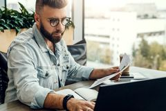 Bärtiger Geschäftsmann, Blogger, der im Café, sprechend am intelligenten Telefon sitzt und arbeiten auf Laptop, Freiberufler, der stockfotografie