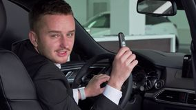 Bärtiger Geschäftsmann, der heraus Auto Schlüssel zur Kamera, sitzend im neuen Automobil hält stock video