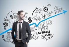 Bärtiger Geschäftsmann und blaues Diagramm auf Beton Stockfotografie