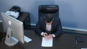 Bärtiger Geschäftsmann unter Verwendung des Smartphone, der am Schreibtisch im Büro sitzt stock footage