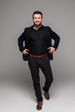 Bärtiger Geschäftsmann in voller Länge im schwarzen Anzug lokalisierte grauen Hintergrund Stockfotos