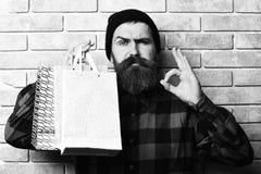 Bärtiger grober kaukasischer Hippie mit dem Schnurrbart, der Einkaufspakete hält lizenzfreies stockbild