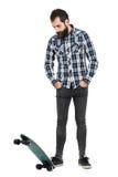 Bärtiger Hippie, der auf longboard Rochen mit den Händen in der Tasche unten schaut steht Lizenzfreie Stockfotografie