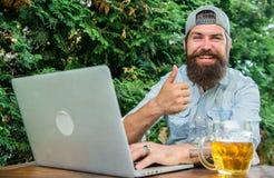 Bärtiger Hippie des Fußballfans machen, Sportspiellaptop zu wetten Kerl sitzen Terrasse draußen mit Bier Wetten und wirkliches Ge lizenzfreies stockbild