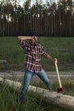 Bärtiger Holzfäller, der in der Hand eine große Axt und Abwischen der Schweiß hält Stockfotos