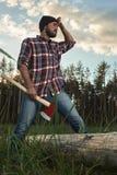 Bärtiger Holzfäller, der eine große Axt in einer Hand und im Abwischen der Schalter hält Lizenzfreies Stockbild