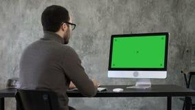 Bärtiger junger Geschäftsmann, der auf Computer woking ist Grüne Schirm-Modell-Anzeige stock video
