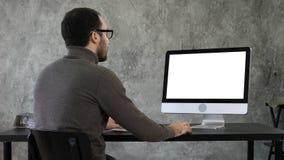 Bärtiger junger Geschäftsmann, der auf Computer woking ist Weiße Bildschirmanzeige lizenzfreie stockbilder