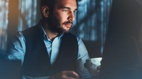 Bärtiger junger Geschäftsmann, der an modernem Büro arbeitet Denkendes Schauen des Beratermannes im Monitorcomputer Manager, der  stockfotos