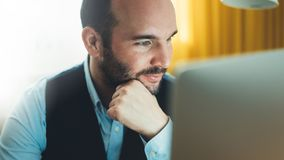 Bärtiger junger Geschäftsmann, der an modernem Büro nachts arbeitet Denkendes Schauen des Beratermannes im Monitorcomputer Manage lizenzfreie stockfotos