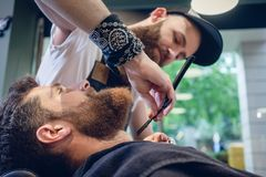 Bärtiger junger Mann bereit zum Rasieren im Friseursalon eines erfahrenen Friseurs stockbilder
