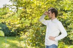 Bärtiger junger Mann, der Augen auf Horizont mit Kopienraum abschirmt Stockbilder