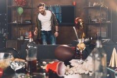 Bärtiger junger Mann mit dem Kater, der im unordentlichen Raum nach Partei steht Lizenzfreie Stockfotografie