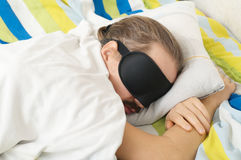 Bärtiger kaukasischer junger Mann, der mit Schlafmaske im Bett schläft Lizenzfreie Stockfotos