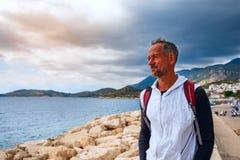 Bärtiger kaukasischer Mann, Reisender, der entlang den Jachthafen geht lizenzfreie stockfotos