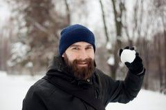 Bärtiger Kerl, der Schneebälle spielt Stockbild