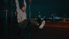 Bärtiger Kerl hängt am Übungsraum im Park in der Nacht und in anhebenden Beinen stock video footage