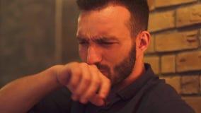 Bärtiger Kerl ist durch ein Cocktail gekrümmt stock footage