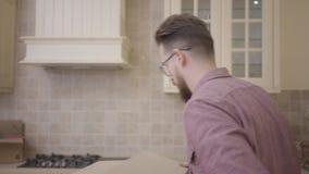 Bärtiger Kerl mit Gläsern holt eine Pappschachtel zur Küche seines neuen Hauses Bewegen auf eine neue Wohnung stock video
