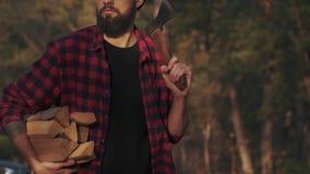 Bärtiger Kerlweg im Wald mit gehackt meldet eine Hand und Axt in seiner Schulter an Förster trägt Brennholz langsam stock video