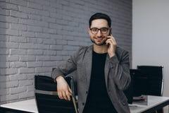 Bärtiger lächelnder Exekutivarbeitskraftmann der attraktiven hübschen jungen Brünette im BüroArbeitsplatz-Arbeitsplatz, sprechend lizenzfreie stockbilder
