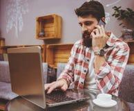 Bärtiger männlicher Hippie mit Telefon lizenzfreies stockfoto