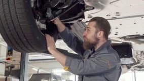 Bärtiger männlicher Mechaniker, der Räder eines Autos auf einem Aufzug an der Garage überprüft stock footage